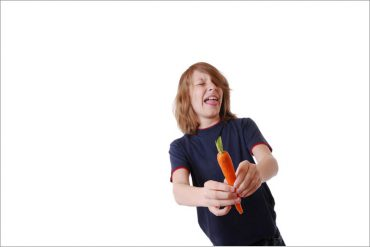 Junge hat keinen Hunger auf Gemüse