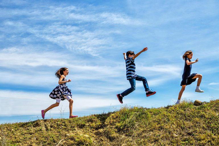 3 Kinder laufen auf der Wiese