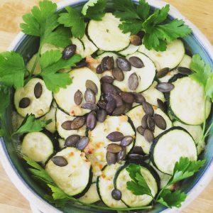 Schüssel mit überbackenen Zucchinischeiben und Kürbiskernen