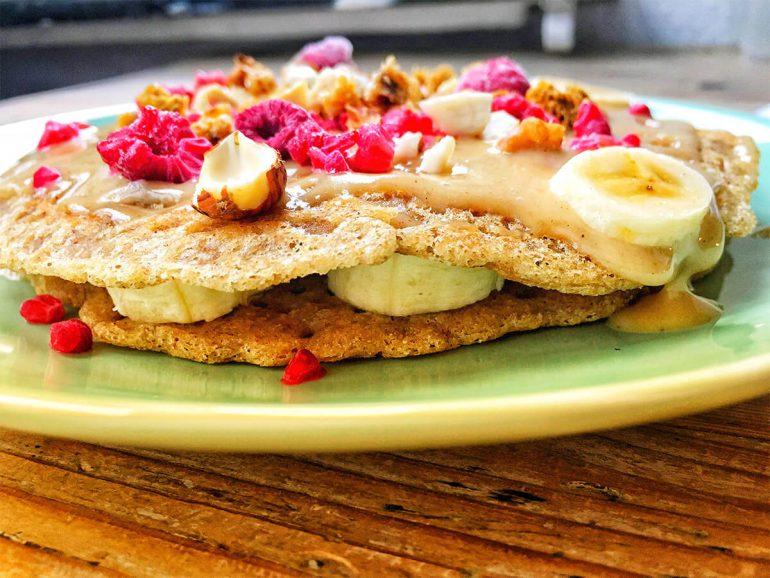 Teller mit Buchweizen Pfannkuchen mit Erdnuss-Sauce und Bananen
